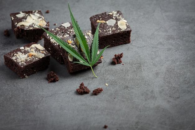 Brownies au cannabis et feuilles de cannabis posées sur un sol sombre