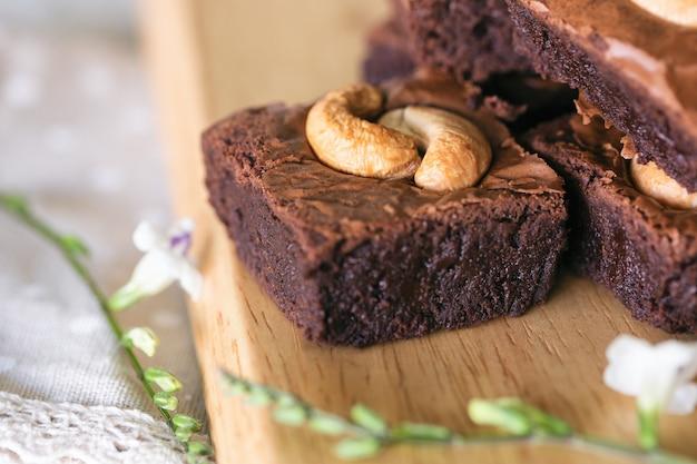 Brownies au chocolat fondant au four avec garniture aux noix de cajou empilées sur une plaque de bois. délicieux goût amer doux, moelleux et brumeux. le brownie est un type de gâteau au chocolat. concept de boulangerie maison.
