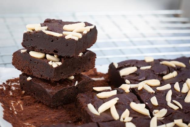 Brownies au chocolat noir avec garniture aux amandes sur une grille.