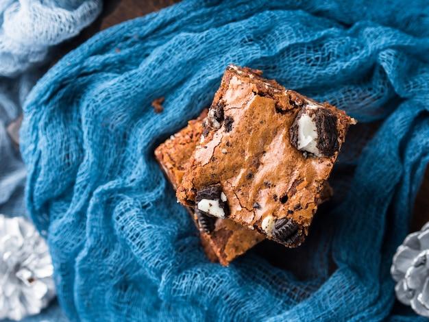 Brownies au fromage à la crème avec des biscuits sur le bleu. friandise de noël en hiver, tablettes de chocolat carrées.