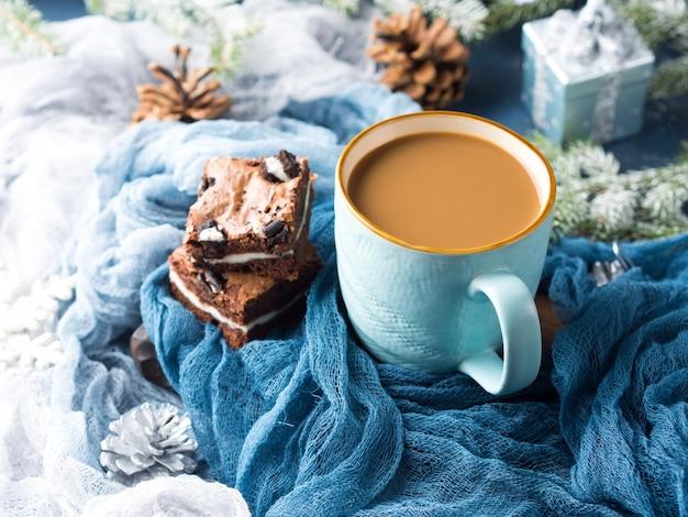 Brownies au fromage à la crème avec des biscuits sur le bleu et une tasse de café et de lait.