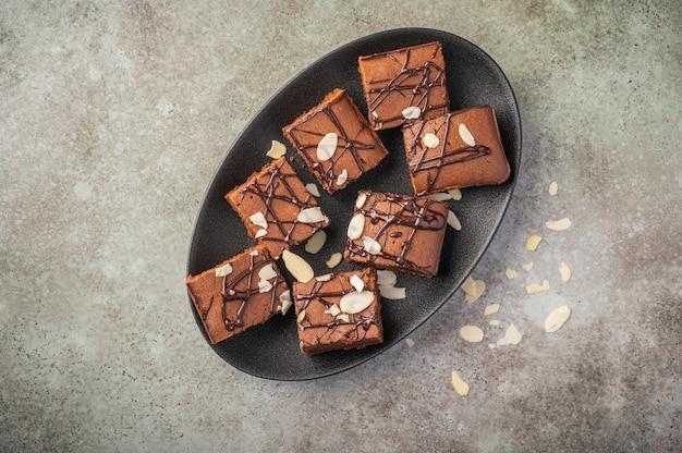 Brownies maison aux pétales d'amande sur une plaque sombre sur un fond en bois.
