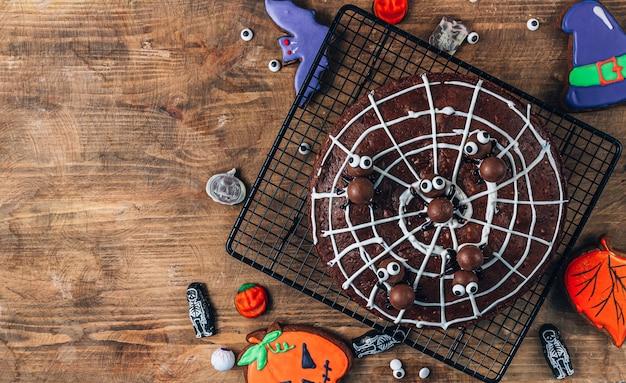 Brownies en toile d'araignée au chocolat avec araignées en bonbons, friandises maison pour halloween sur fond de bois rustique. vue de dessus avec espace de copie