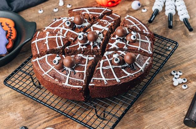 Brownies de toile d'araignée au chocolat avec des araignées en bonbons, friandises maison pour halloween sur fond de bois rustique