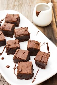 Brownies en tranches sur une plaque blanche. avec une garniture au chocolat et au fudge.