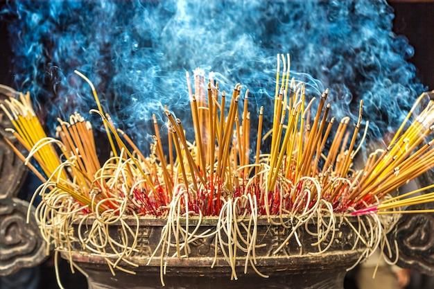 Brûler des bâtons d'encens dans la pagode tran quoc à hanoi, vietnam