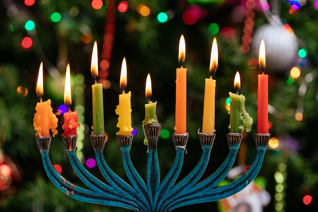 Brûler des bougies de hanukkah dans une menorah sur fond bleu