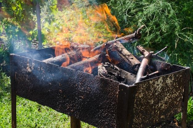 Brûler du bois de chauffage dans le barbecue. feu de joie pour un pique-nique. journée d'été ensoleillée à l'extérieur.