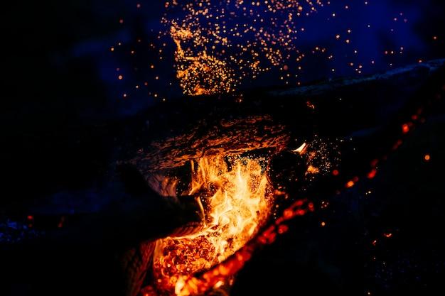 Brûler du bois la nuit avec des flammes et des étincelles de feu