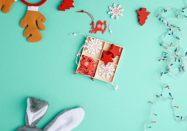 Brûler une guirlande de noël sur un fil blanc avec des lumières colorées et une boîte avec des jouets en bois pour l'arbre de noël