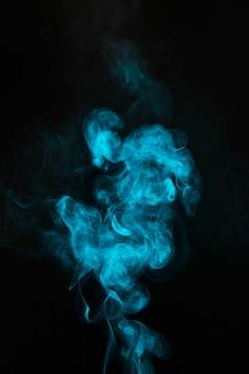 Brume bleue soufflant de la fumée sur fond noir