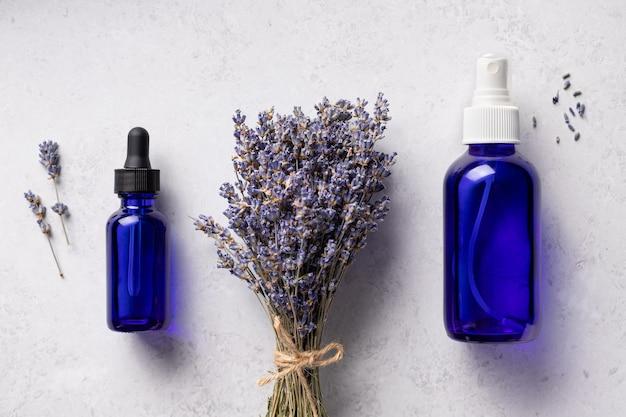 Brume d'huile essentielle de lavande dans des bouteilles bleues traitement d'aromathérapie cosmétiques naturels de spa