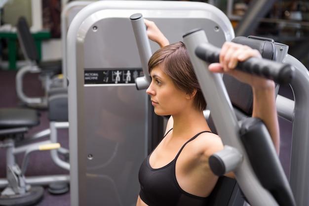 Brune athlétique en utilisant des poids machine pour les bras