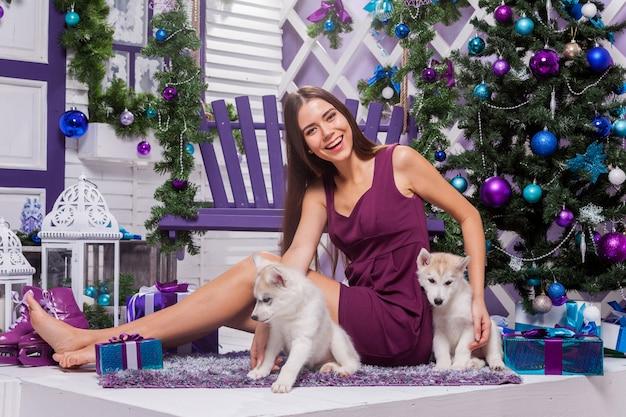 Brune aux longues jambes dans une robe bordeaux assis sur un tapis violet