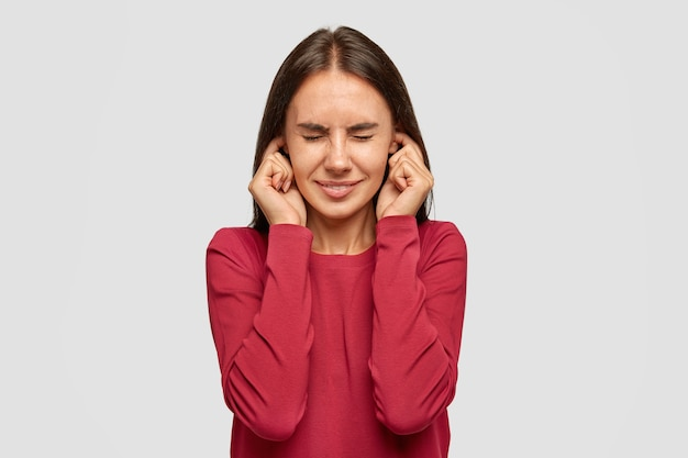Une brune aux taches de rousseur stressante se bouche les oreilles