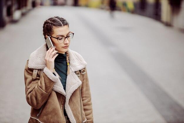 Brune ayant une conversation téléphonique dans la rue. elle est inquiète.