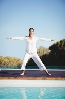 Brune calme faisant du yoga au bord de la piscine