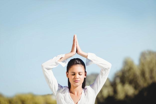 Brune calme faisant du yoga par une journée ensoleillée