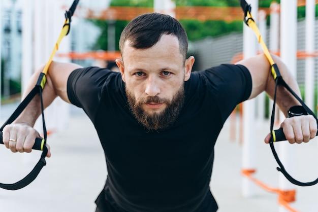 Une brune concentrée avec une barbe est engagée en plein air. l'homme est engagé dans le crossfit, effectue des exercices avec persistance, regarde la caméra