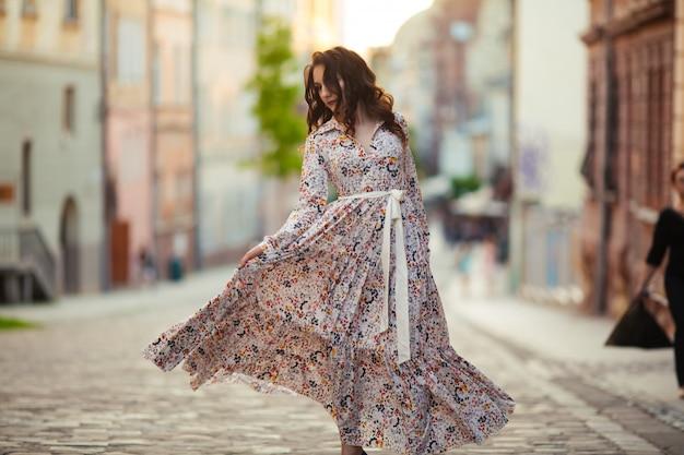 Une brune danse dans les rues de lviv dans une belle robe longue