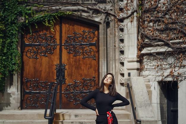 Brune élégante debout à côté de l'entrée d'un bâtiment
