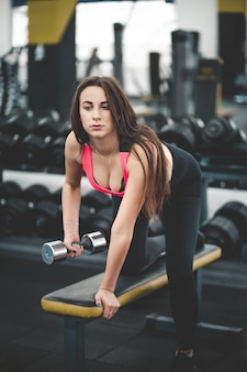 Brune fait du fitness dans la salle de gym.