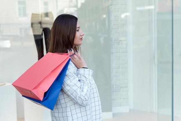 Brune fatiguée tenant des sacs à provisions sur fond de vitrine. vendredi noir. achats épuisants.