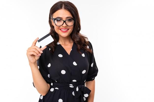 Brune à lunettes détient une carte de crédit sur un mur blanc avec copie espace