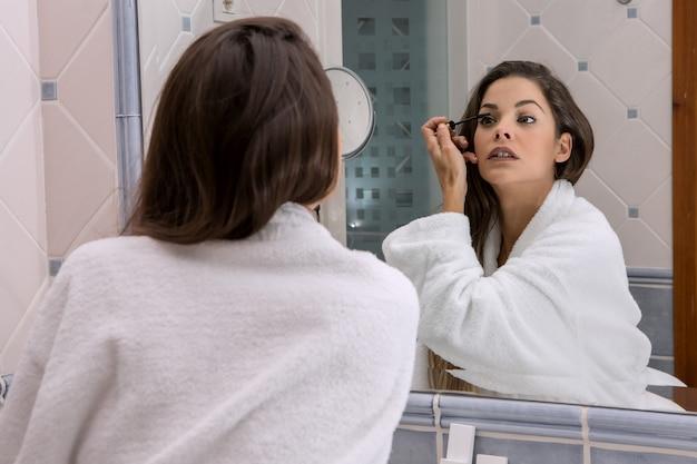 Brune sensuelle en peignoir se maquillant
