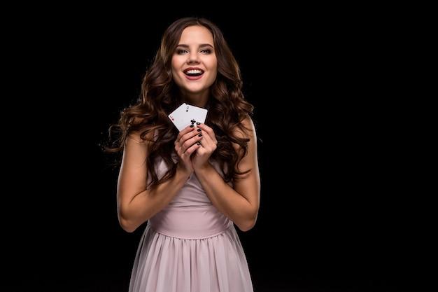 Brune sexy aux cheveux bouclés posant avec des jetons dans ses mains, fond noir de concept de poker