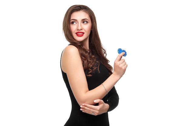 Brune sexy aux cheveux bouclés posant avec des jetons dans ses mains, isolement du concept de poker sur fond blanc