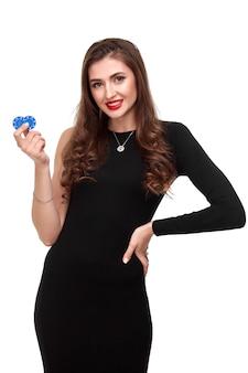 Brune sexy aux cheveux bouclés posant avec des jetons dans son isolement de concept de poker mains sur fond blanc