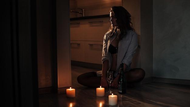 Une brune sexy dans un soutien-gorge noir et une chemise d'homme est assise sur le sol par une fille séduisante aux chandelles