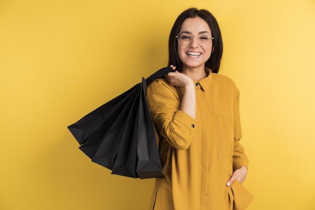 Une brune souriante se réjouit de ses achats sur un mur jaune