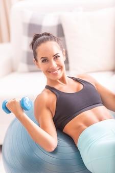 Une brune souriante tient des haltères à main faisant des exercices de biceps sur une balle en forme.