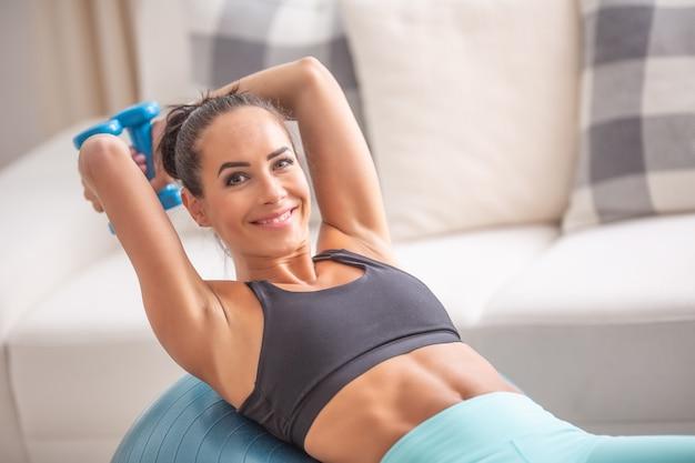 Une brune souriante tient des haltères à main faisant des exercices de triceps sur une balle en forme.