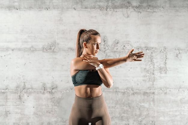 Brune sportive ciblée avec queue de cheval et bras d'étirement sportswear avant de s'exercer devant un mur rustique gris.
