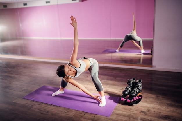Brune sportive saine qui s'étend des jambes et du dos en se tenant debout sur le tapis dans la salle de gym. à côté de ses chaussures kangoo jumps