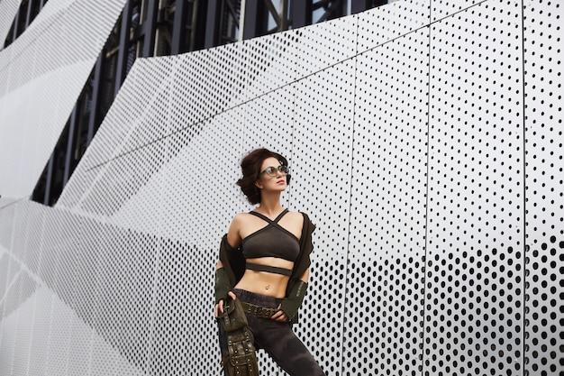 Brune sportive et sexy, fille modèle de fitness avec un corps parfait dans des lunettes de soleil élégantes et dans une tenue militaire avec des motifs de camouflage, enlève son gilet et pose à l'extérieur dans une ville