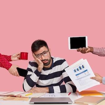Brunet homme assis au bureau entouré de gadgets et de papiers