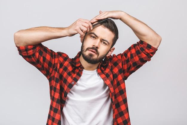 Brunet homme peignant ses cheveux avec une brosse à cheveux, tenant la main sur la tête, isolé sur fond blanc.