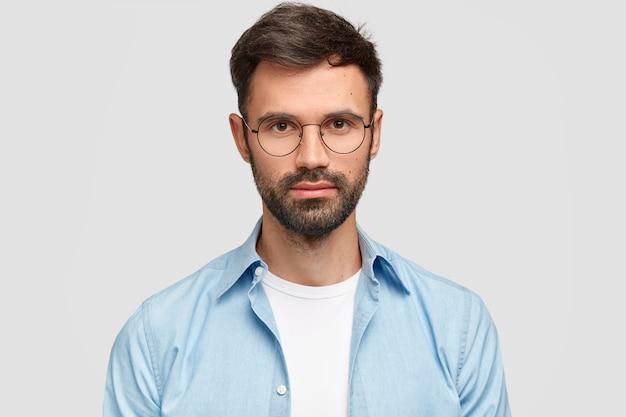Brunet homme portant des lunettes rondes et chemise bleue