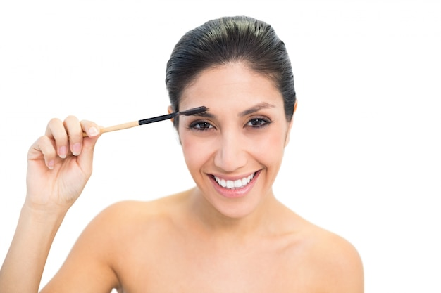 Brunette à l'aide d'une brosse à sourcils et souriant