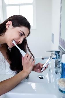 Brunette à l'aide de smartphone en se brossant les dents dans la salle de bain