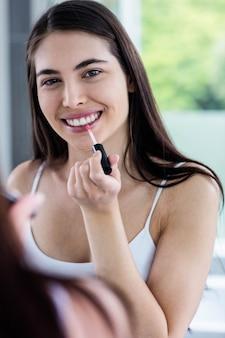 Brunette appliquant le brillant à lèvres dans la salle de bain