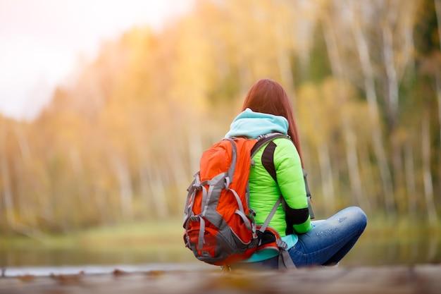 Brunette assise sur le pont en automne