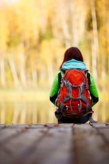 Brunette assise avec sac à dos sur le pont près de l'eau