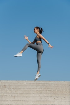 Brunette athlétique exerçant à l'extérieur sous un ciel bleu clair