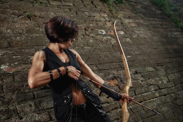Brunette athlétique tirant avec l'arc et la focalisation de tacking.