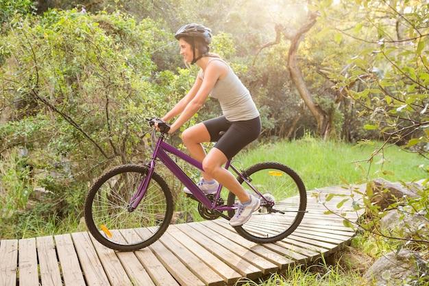 Brunette athlétique vtt sur sentier en bois